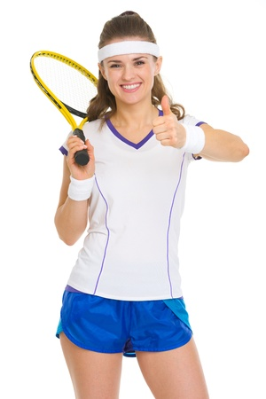 Smiling female tennis player with racket showing thumbs up photo