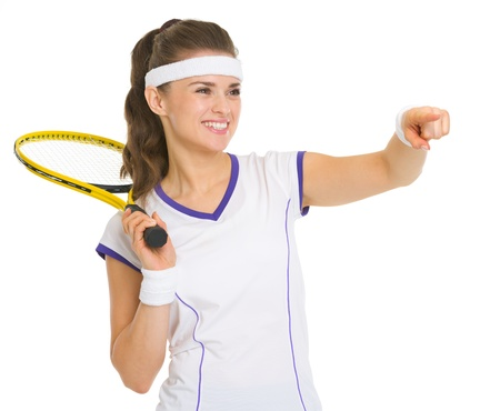 Smiling female tennis player with racket pointing on copy space photo