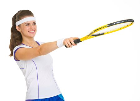 Smiling female tennis player pointing with racket on copy space photo