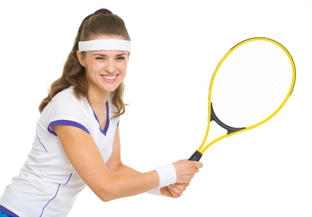 Smiling female tennis player ready to hit ball photo