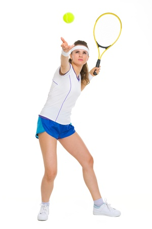 Full length portrait of female tennis player serving ball photo