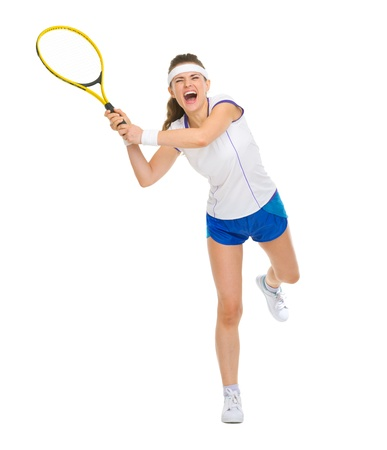 Full length portrait of female tennis player hitting ball photo