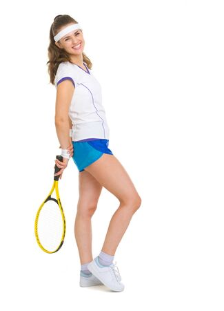 Full length portrait of smiling female tennis player with racket photo