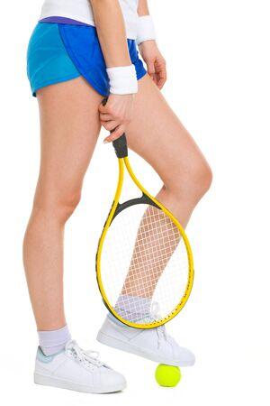 Closeup on female tennis player standing with one foot on ball photo
