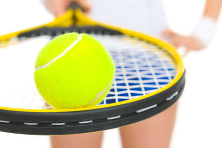 Closeup on female tennis player holding racket with ball photo