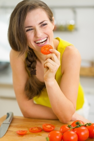 Smiling young woman eating tomato Stock Photo - 19093432