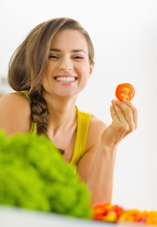 Portrait of happy young woman with tomato in kitchen Stock Photo - 19093459