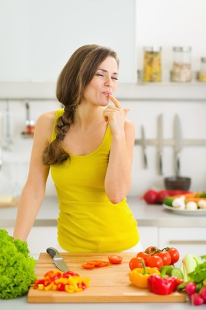Happy young housewife tasting vegetables while cutting photo