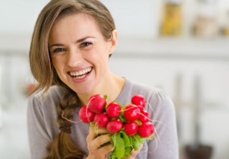 Portrait of smiling young woman with bunch of radishes Stock Photo - 19093519