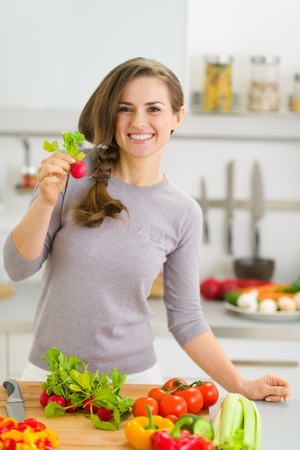 Happy young housewife in modern kitchen showing radish photo