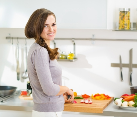 Happy young housewife cutting fresh vegetables in modern kitchen Stock Photo - 19093416