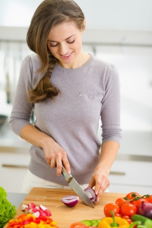 Happy young housewife cutting onion in modern kitchen photo