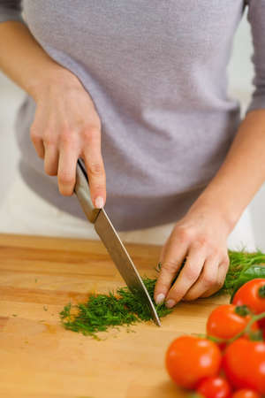 Closeup on woman cutting fresh dill photo