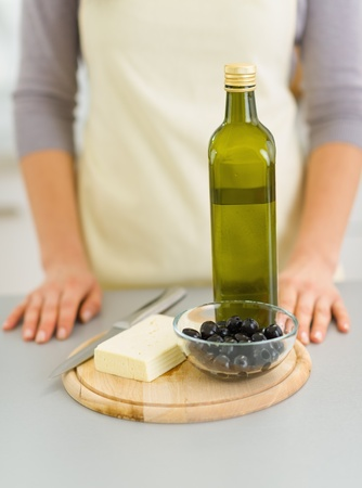 Closeup on cheese, olives and olive oil on cutting board photo