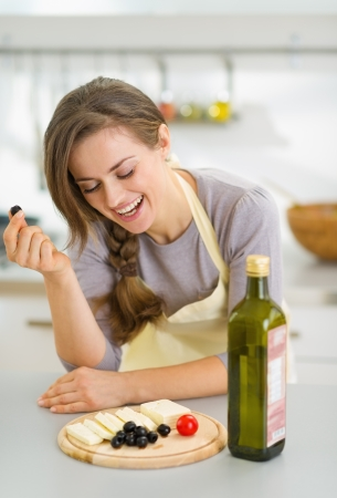 Happy young woman eating fresh cheese and olives photo