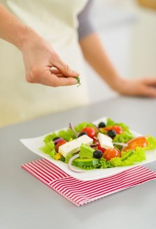 Closeup on woman adding fresh dill into salad Stock Photo - 19093451