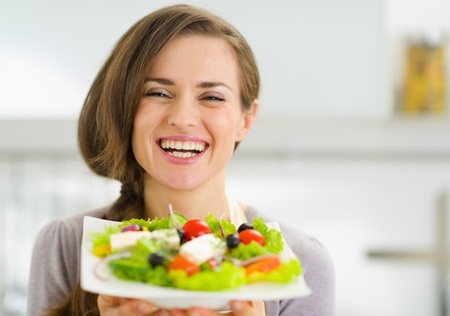 Smiling young woman showing fresh salad Stock Photo - 19093434