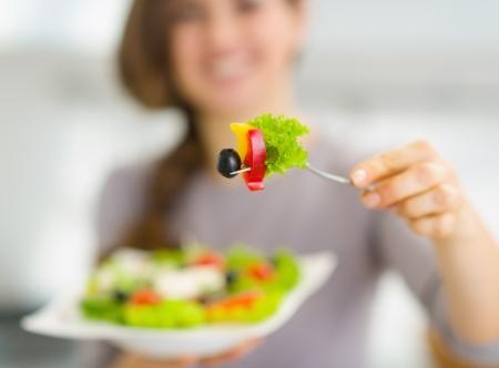 Close-up op vork met salade in de hand van jonge vrouw Stockfoto