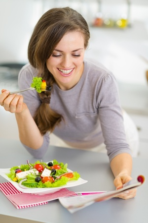 Happy young housewife eating fresh salad and reading magazine in kitchen Stock Photo - 19093544