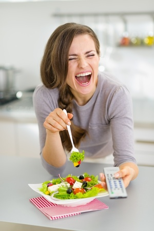 Laughing young woman eating salad and watching tv in kitchen photo