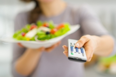Closeup on tv remote control and fresh salad in hand of young woman photo