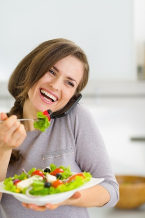 Smiling young woman eating salad and talking mobile phone photo