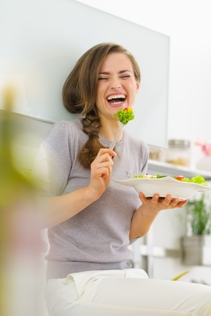 Smiling young woman eating fresh salad in modern kitchen Stock Photo
