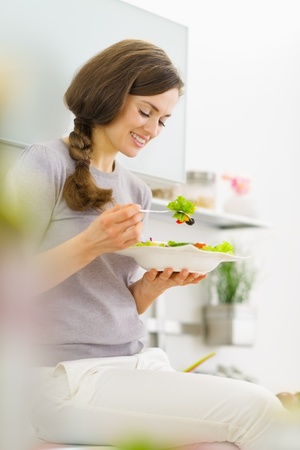 eating breakfast: Young woman eating fresh salad in modern kitchen