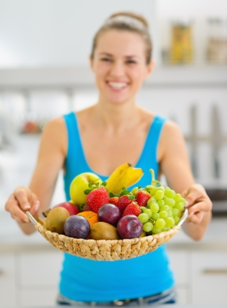 Closeup on plate of fresh fruits giving by smiling young woman photo