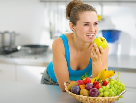 Happy young woman eating apple in modern kitchen photo