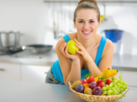 Smiling young woman holding apple in modern kitchen photo