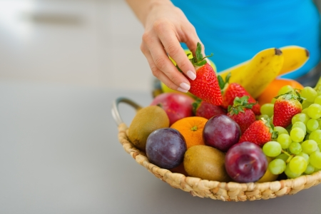Closeup on female hand taking strawberry from plate of fresh fruits Stock Photo - 19093537