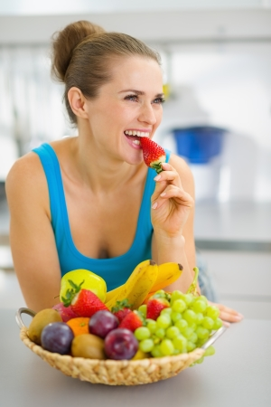 Happy young woman eating strawberry in modern kitchen photo