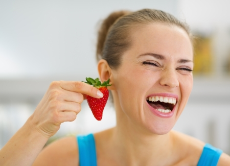 Laughing young woman using strawberry as earring Stock Photo - 19093438