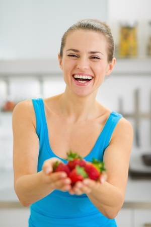 Happy young woman giving strawberries Stock Photo - 19093444