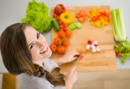 Happy young housewife cutting fresh vegetables Stock Photo