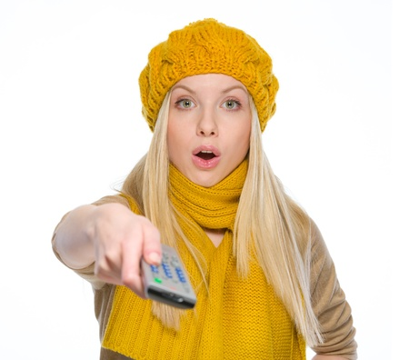Surprised girl in autumn clothes using tv remote control Stock Photo - 19226704