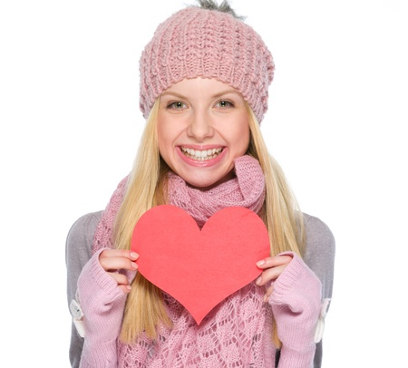 Portrait of smiling girl in winter clothes showing heart shaped postcard photo