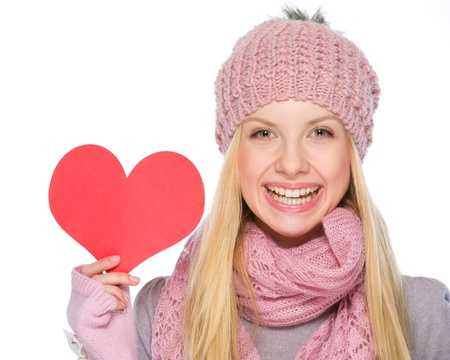 Portrait of happy girl in winter clothes showing heart shaped postcard photo
