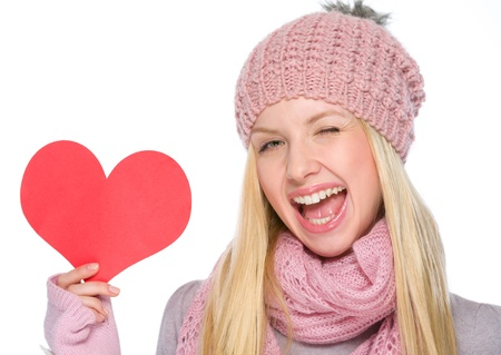 Portrait of girl in winter clothes showing heart shaped postcard and winking photo