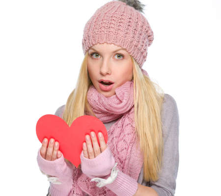 Surprised girl in winter clothes reading heart shaped postcard photo