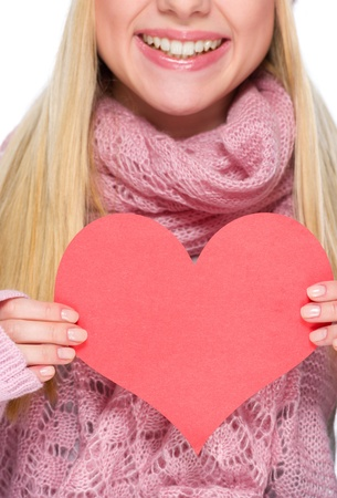Closeup on heart shaped postcard in hand of girl in winter clothes photo