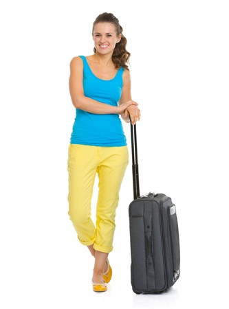 Full length portrait of smiling young tourist woman with wheel bag photo