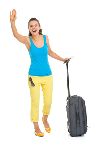 Full length portrait of happy young tourist woman with wheel bag saluting photo