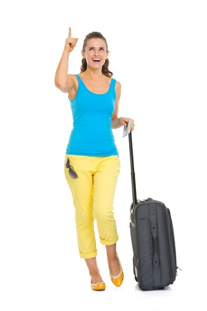 Happy young tourist woman with wheel bag pointing on copy space photo