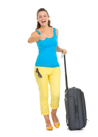 Full length portrait of happy young tourist woman with wheel bag showing thumbs up photo
