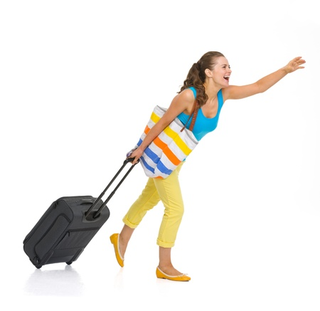 Full length portrait of young tourist woman with wheel bag catching taxi photo