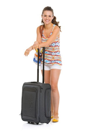 Full length portrait of happy young tourist woman with wheel bag photo