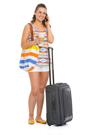 Young tourist woman with wheel bag talking mobile phone photo