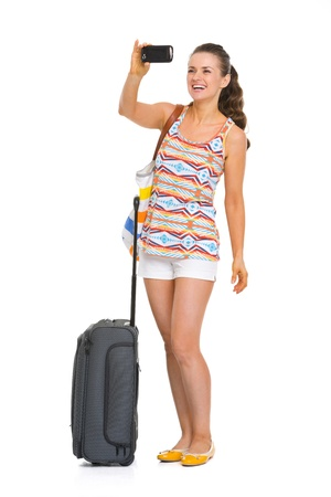 Happy young tourist woman with wheel bag taking photos Stock Photo - 19339977